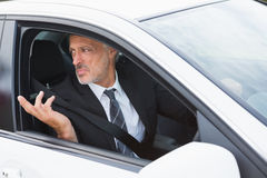 Perplexed businessman in the drivers seat Royalty Free Stock Photos
