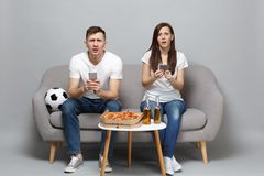 Perplexed couple woman man football fans cheer up support favorite team, sitting holding using mobile phone isolated on. Perplexed couple women men football fans stock photo