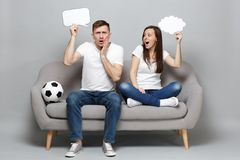 Perplexed couple woman man football fans cheer up support favorite team with soccer ball hold empty blank Say cloud royalty free stock photography