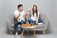 Perplexed couple woman man football fans in white t-shirt cheer up support favorite team with soccer ball isolated on. Perplexed couple women men football fans stock image