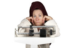Perplexed Dieter. Mature woman in bathrobe standing on a bathroom scale looking perplexed Royalty Free Stock Image