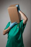 Perplexed doctor with cardboard box head Stock Photo