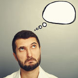 Perplexed man looking at speech bubble Royalty Free Stock Image
