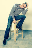 Perplexed man sitting on stool, holding his head for  problems Stock Images