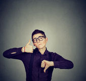 Perplexed man with thumbs down thumbs up gesture looking up Royalty Free Stock Photos