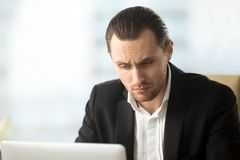 Perplexed young businessman looking at laptop screen at workplac Stock Photos