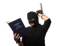 Perplexed robber with gun reads book over white. Stock Images