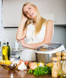 Perplexed woman with fish and multicooker Stock Photos