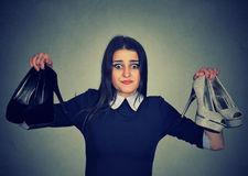 Perplexed woman keeps two stylish pumps can`t choose one for her Stock Image