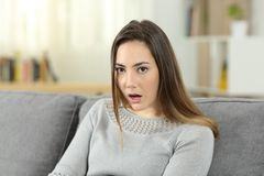 Perplexed woman looking at camera at home. Portrait of a perplexed woman looking at camera sitting on a couch in the living room at home. She does not believe Stock Photo