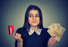 Perplexed woman shopper holding credit card and euro cash banknotes. Royalty Free Stock Photos