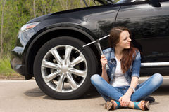 Perplexed woman waiting for roadside assistance. Perplexed young woman waiting for roadside assistance after her car breaks down at the side of the road sitting Royalty Free Stock Image