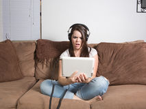 Perplexed woman watching streaming media on tablet Stock Photo