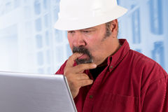 Perplexed at Work. Hardhat worker perplexed, working on the tough issues with his laptop, he has a serious thoughtful look that he values his job, he is wearing Royalty Free Stock Photo
