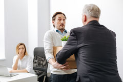 Perplexed worker receiving the box with belongings from the employer. Stressful situation . Frustrated shocked puzzled men standing and getting the box with Royalty Free Stock Photography