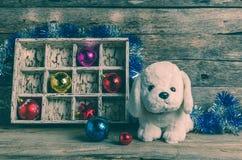 Perrito blanco en el fondo de las decoraciones de la Navidad, año del perro Fotos de archivo