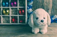 Perrito blanco en el fondo de las decoraciones de la Navidad, año del perro Imagenes de archivo