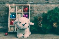 Perrito blanco en el fondo de las decoraciones de la Navidad, año del perro Fotografía de archivo