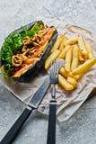 Perrito caliente con kebab de la carne de vaca y las cebollas caramelizadas Fondo gris, vista lateral fotos de archivo libres de regalías