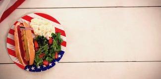 Perrito caliente con la bandera americana en placa Foto de archivo