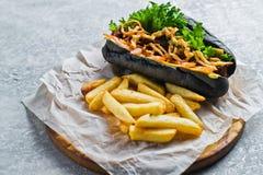 Perrito caliente con la salchicha de la carne de vaca y las cebollas caramelizadas en un bollo negro Fondo gris, visi?n superior, fotografía de archivo