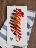 Perrito caliente con la salsa de tomate en una placa blanca imagenes de archivo