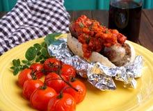 Perrito caliente con la salsa del tocino y de tomate Imagenes de archivo