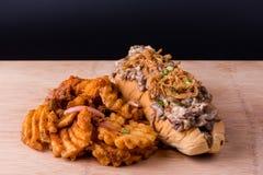 Perrito caliente con las fritadas de la cebolla y del desmoche y de la galleta de la carne de vaca Foto de archivo