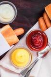 Perrito caliente en la tabla de madera con la salsa de tomate, la mayonesa y la mostaza en grasteler imagenes de archivo