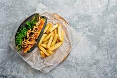Perrito caliente negro con kebab de la carne de vaca y las cebollas caramelizadas Fondo gris, visi?n superior, espacio para el te foto de archivo