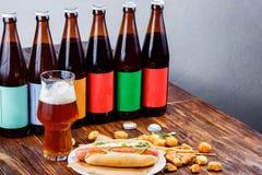 Perrito caliente y cerveza en un tablero de madera Imágenes de archivo libres de regalías