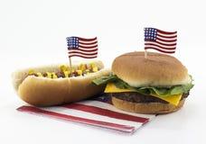 Perrito caliente y hamburguesa en una servilleta y un palillo de la bandera americana imágenes de archivo libres de regalías