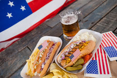 Perrito caliente y vidrio de cerveza con la bandera americana en la tabla de madera Imagenes de archivo