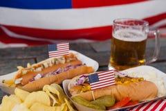 Perrito caliente y vidrio de cerveza con la bandera americana en la tabla de madera Foto de archivo