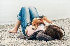 Perrito del beagle que duerme en su pecho del dueño en el lado de mar imagen de archivo libre de regalías
