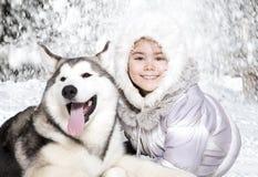 Perrito del Malamute con una muchacha Fotografía de archivo