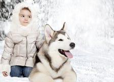 Perrito del Malamute con una niña Imagenes de archivo