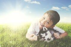Perrito fornido del abarcamiento del muchacho en el prado Imágenes de archivo libres de regalías
