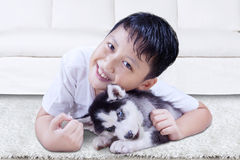 Perrito fornido del abarcamiento feliz del muchacho en casa Foto de archivo
