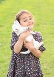Perrito holded en manos de los niños Fotos de archivo