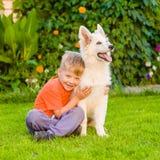 Perrito suizo blanco del ` s del pastor del abarcamiento del muchacho en hierba verde Imagenes de archivo