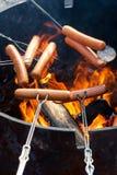Perritos calientes de la asación sobre el fuego Imagen de archivo libre de regalías