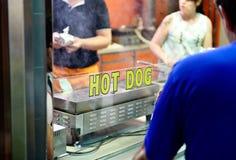 Perritos calientes de la compra de la gente en el parque de atracciones Imagenes de archivo
