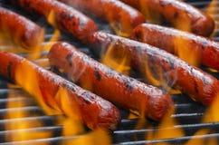 Perritos calientes en una parrilla caliente llameante de la barbacoa Foto de archivo libre de regalías
