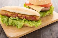 Perritos calientes, hamburguesas en el fondo de madera Imagenes de archivo