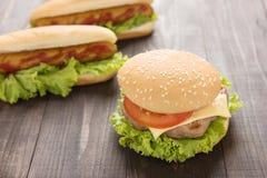 Perritos calientes, hamburguesas en el fondo de madera Fotografía de archivo