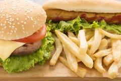 Perritos calientes, hamburguesas y patatas fritas en el fondo de madera Imagenes de archivo