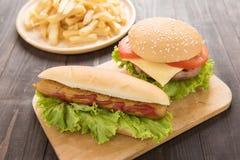 Perritos calientes, hamburguesas y patatas fritas en el fondo de madera Fotografía de archivo