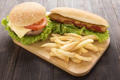 Perritos calientes, hamburguesas y patatas fritas en el fondo de madera Fotos de archivo libres de regalías