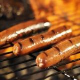 Perritos calientes que cocinan en parrilla llameante Imagenes de archivo